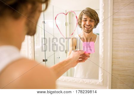 Boyfriend discovering a love message on the mirror in the bathroom at home