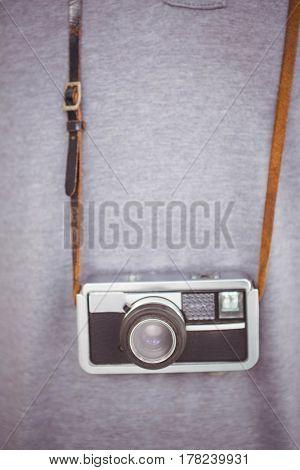 Handsome hipster holding retro camera around hipster neck