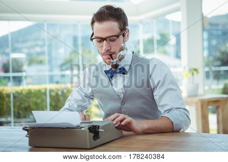 Handsome man using old fashioned typewriter in bright office