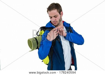 Backpacker adjusting his backpack on white background
