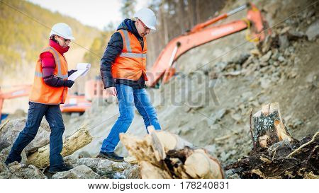 Road engineer workers inspecting road reconstruction and processes