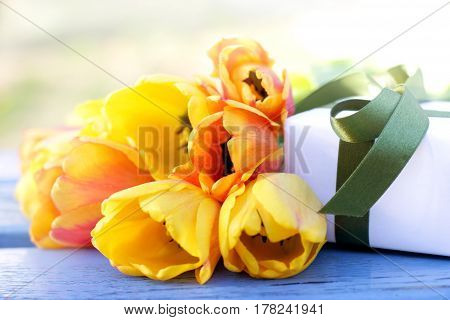 Yellow red tulips with a gift in a box / congratulations on a holiday
