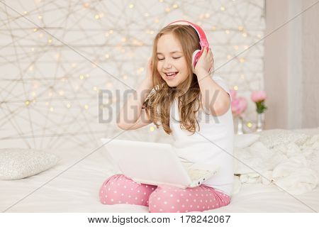 Music and technology. Portrait of young girl in pajamas with white laptop and wireless pink headphones, sing song on background with lights. Pastel colors, indoor