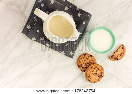 An overhead photo of chocolate chips cookies in front of a glass of milk and a milk jar, with a place for text