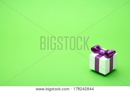 Gifts in a beautiful package, bow from satin ribbon, a few boxes with gifts, attributes festive mood, the gift set on a green background