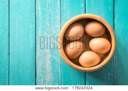 eggs in a wooden bowl on the ocean blue table view from above.
