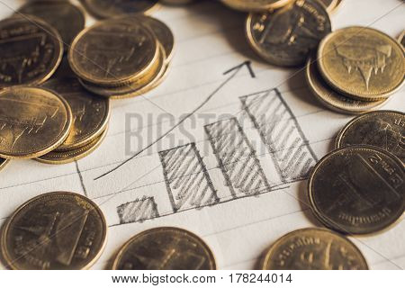 pencil draw business graph on notebook paper with coins business concept.