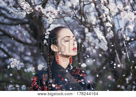 Attractive asian woman wearing kimono standing in blossoming garden. Concept of meditation, dreaming, wellbeing and healthy lifestyle. Gorgeous creative portrait outdoor on the nature. Petals fall down. Female dreaming with closed eyes