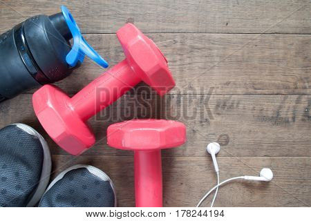 Flat lay of fitness and workout accessories red dumbbells water bottle and sneakers on wood background