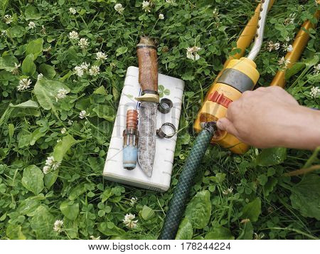Male hand fixing a garden hose laid on the grass work tools and hose clamps spread out around