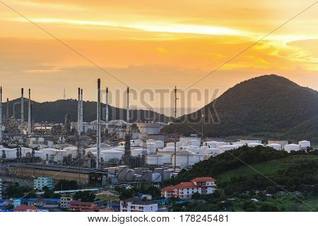 Oil Refinery factory in the sunset , petrochemical plant , Petroleum. and city around area