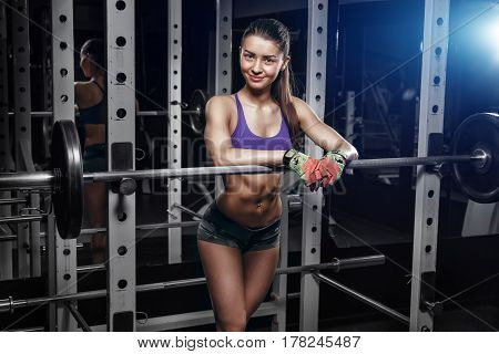 sexy young girl resting after squat exercises. Fitness brunette woman