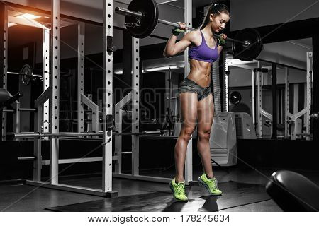 Sexy sporty woman posing in gym with bar