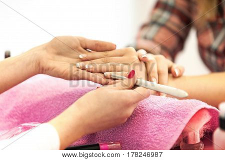 Manicure specialist clearing cuticle professionally. Close up.
