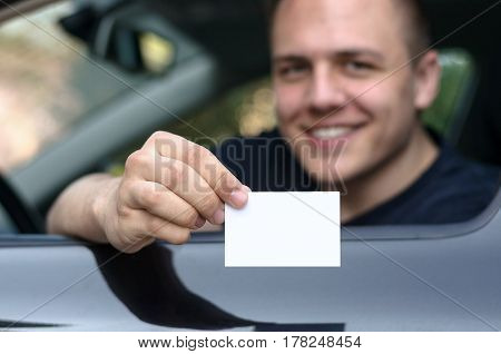 Young Man Leaning From A Car Showing His Licence