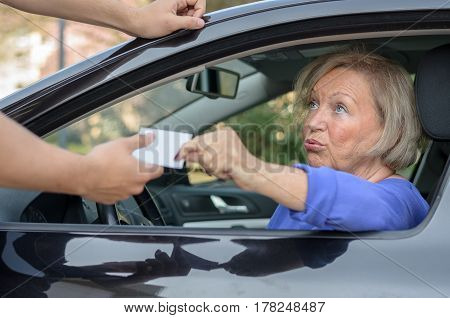 Concerned elderly woman driver handing over her licence to a man reaching towards the open window during a road block or after committing a minor offence poster