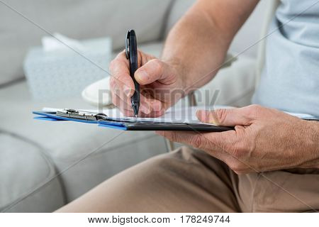 Man writing on notepad at home