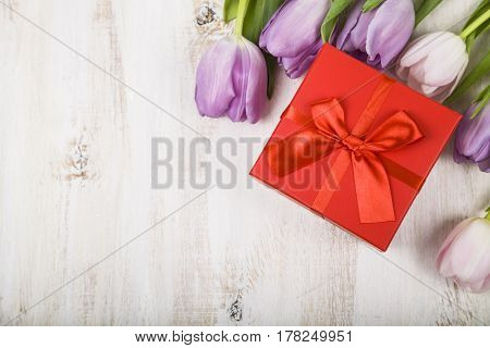 Bouquet Of Tulips And A Gift On A Wooden Background.