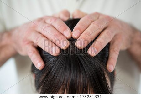 Close-up of woman receiving a head massage from masseur at the health spa