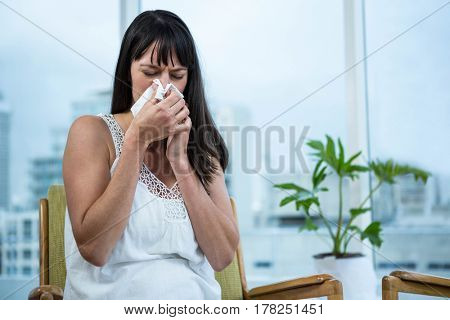 Pregnant woman wiping nose at home