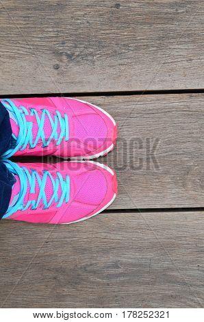 Woman Leg With Pink Sport Shoe On Brown Wood Slat Floor