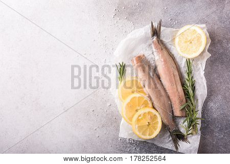 Freshly salted herring with salt, lemon ans rosemary on gray background with copy space. Traditional Dutch delicacy. Retro style toned. Top view.