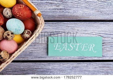 Easter card and egg basket. Eggs and gray wooden planks. Organize an Easter picnic.