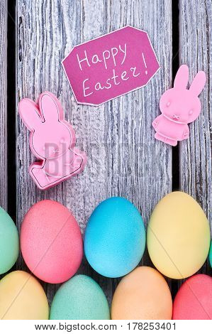 Bright Easter eggs, gray wood. Plastic rabbits and greeting card. Cheap Easter merchandise.