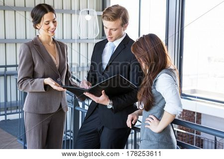 Three confident colleagues discussing in office near staircase