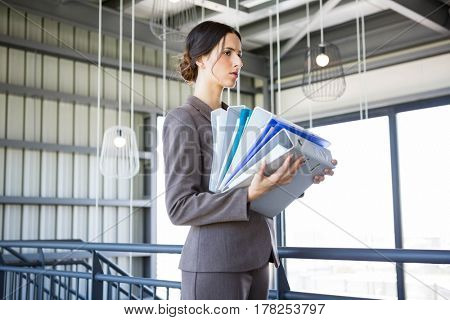 Tired overworked busy businesswoman carrying stack of folders with files documents