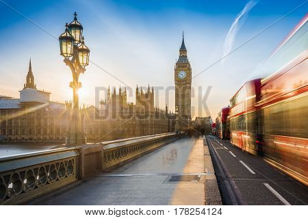 London England - The iconic Big Ben and the Houses of Parliament with lamp post and moving famous red double-decker buses on Westminster bridge at sunset with blue sky