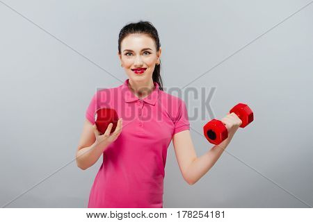 Young Asian woman training muscular and apple of hand with red dumbbells , kg.