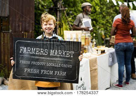 Little Boy Showing Farmers Market Board