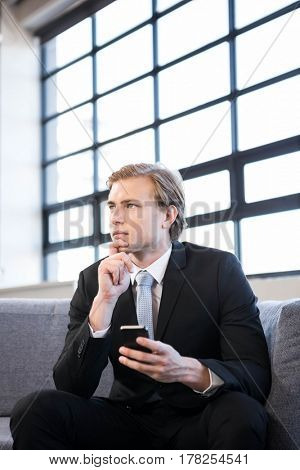 Thoughtful businessman sitting on sofa and looking away in office
