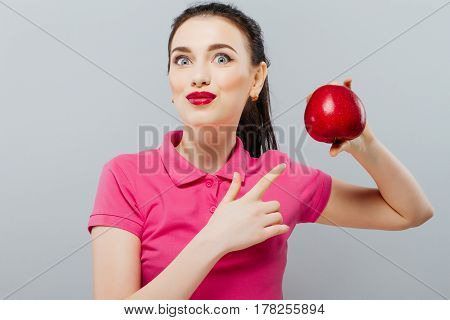 Young beautiful sexy girl with dark hair, holding big red apple to enjoy the taste and dieting, healthy eating and organic foods
