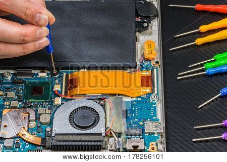 Person Hands Repairing Laptop Motherboard On Carbon Background With Rainbow Collection Of Screwdrive