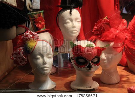Several mannequin faces with colorful hats or masks in storefront window