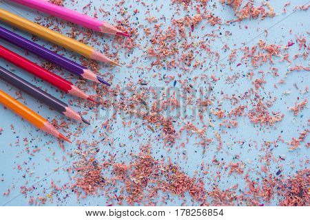 Colour Pencils With Sharpening Shavings Isolated On Cyan With Copy Space