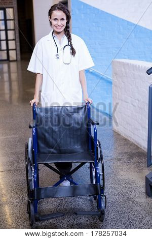 Portrait of female doctor standing with wheel chair in hospital