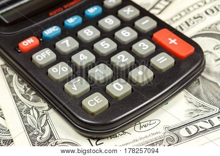 Electronic calculator on the background of US dollars banknotes