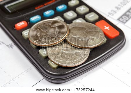 Coins lying on the surface of the electronic calculator. Focus in the foreground