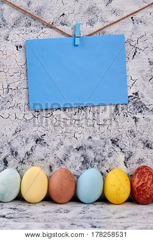 Easter eggs, blank blue card. Empty paper, rope and clothespin.