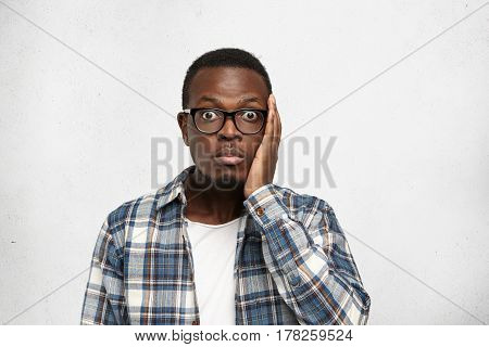 Close Up Portrait Of Amazed African American Guy In Checkered Shirt Holding His Head With Hand, Full