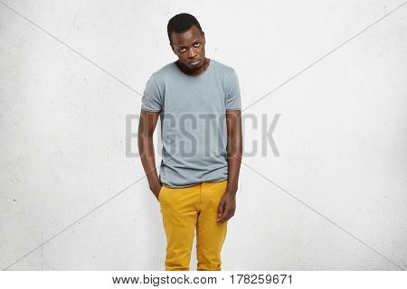 I'm So Sorry. Cropped Portrait Of Attractive African Male In Casual T-shirt And Mustard Pants, Looki