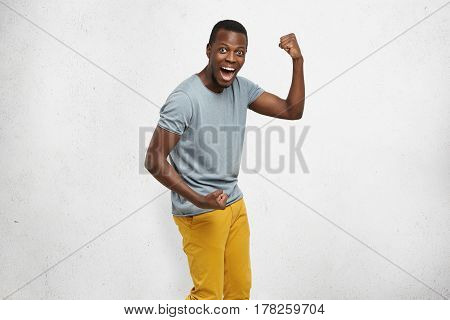 Yes! Indoor Shot Of Handsome Excited Lucky Young African American Student Exclaiming In Excitement,