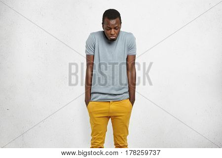 Studio Portrait Of Young African Male Shrugging Shoulders And Looking Down With Guilty Confused Expr