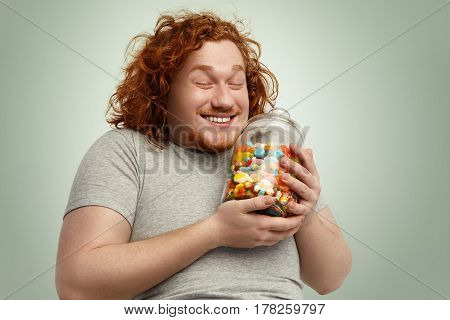 Happy Young Fat Obese Man Smiling Joyfully, Keeping Eyes Closed Rejoicing At Glass Jar Of Goodies, C