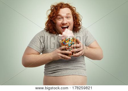 Excited Happy Obese Young Man With Ginger Curly Hair Opening Mouth Widely While Eating Candy Floss O