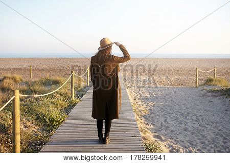 People, Lifestyle And Recreation Concept. Stylish Young Woman Dressed In Warm Coat, Holding Brim Of