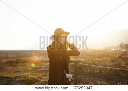 Beautiful Picture Of Young European Female Dressed In Overclothes Adjusting Brims Of Her Stylish Hat